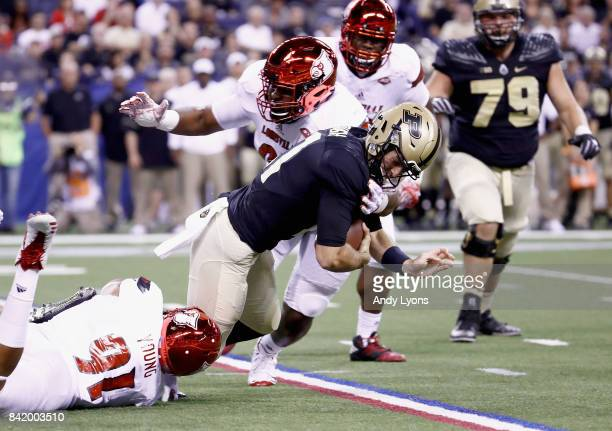 David Blough of the Purdue Boilermakers is sacked by Trevon Young and GG Robinson of the Louisville Cardinals at Lucas Oil Stadium on September 2...