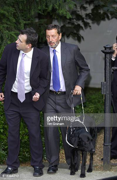 David Blunkett with his guide dog for the blind and an aide to help him in London United Kingdom