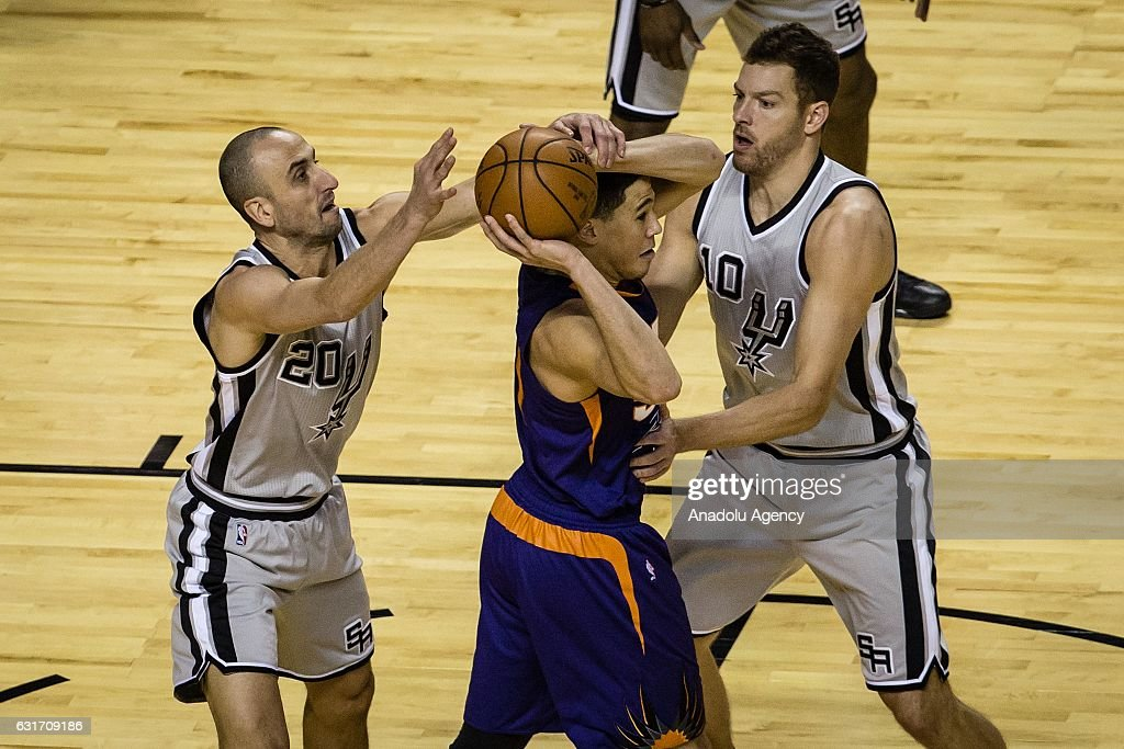 David Booker (C) of the Phoenix Suns struggle for the ball with Manu Ginobili (L) and David Lee (R) of the San Antonio Spurs during the NBA Game Mexico City between Phoenix Suns and San Antonio Spurs at Arena Ciudad de Mexico, in Mexico City, Mexico on January 14, 2017.