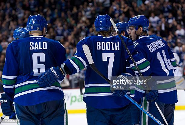David Booth of the Vancouver Canucks celebrates with Sami Salo and Alexandre Burrows after scoring against the Buffalo Sabres during the second...