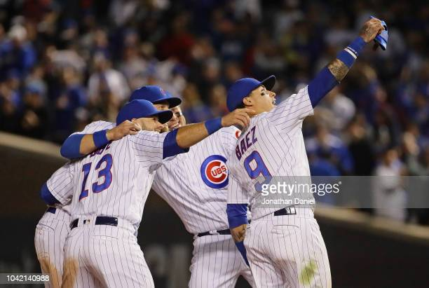 David Bote Ben Zobrist Anthony Rizzo and Javier Baez of the Chicago Cubs pretend to take a selfie after a win over the Pittsburgh Pirates at Wrigley...