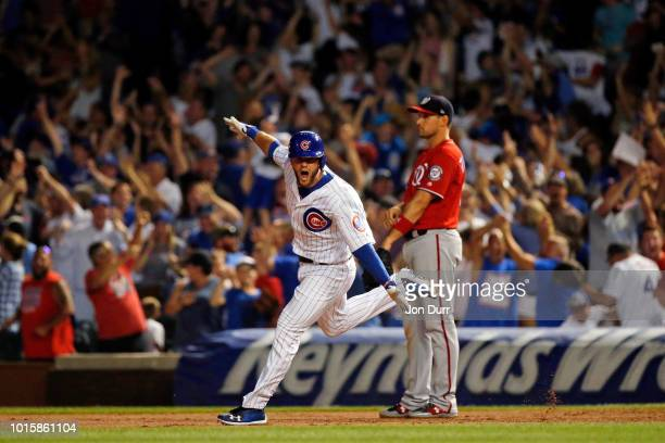 David Bote of the Chicago Cubs celebrates his walkoff grand slam as Ryan Zimmerman of the Washington Nationals looks on at Wrigley Field on August 12...