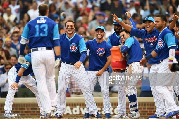 David Bote of the Chicago Cubs is greeted at home plate by teammates after hitting a walk off home run against the Cincinnati Reds during the tenth...