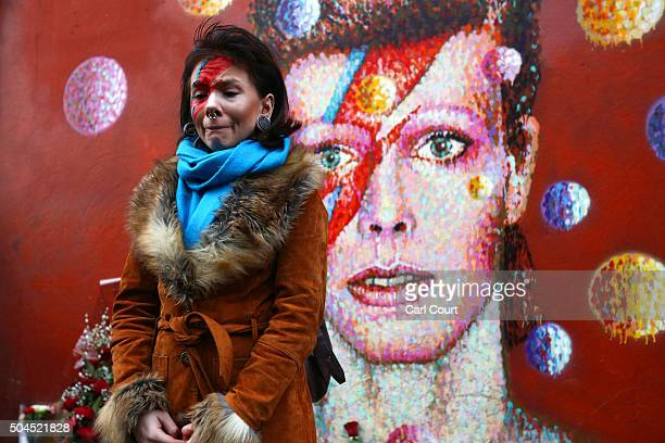 David Bowie fan Rosie Lowery pauses after laying flowers at his mural in Brixton on January 11 2016 in London England British music and fashion icon...