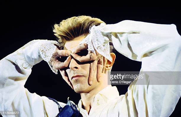 David Bowie looking through his fingers during a performance at the Milton Keynes Bowl 1990