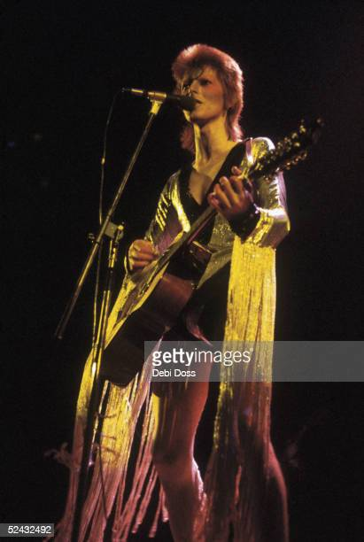 David Bowie performing as Ziggy Stardust at the Hammersmith Odeon 1973 He is wearing a silver costume with gold tassels by Japanese designer Kansai...