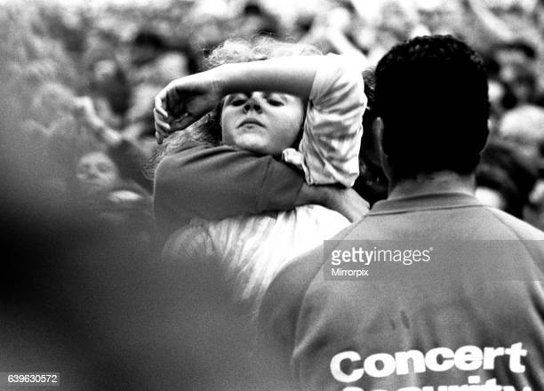 David Bowie performing at Roker Park Sunderland on 23rd June 1987 in his Glass Spider Tour A girl who has fainted being brought to the front