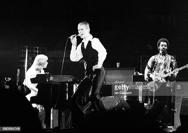 David Bowie performing on stage with Tony Kaye and Carlos Alomar at Wembley Arena London 03 May 1976