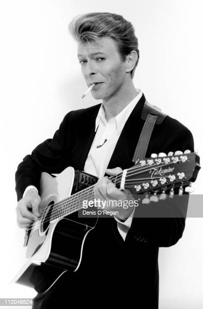 David Bowie poses with a Takamine twelvestring guitar at the Rainbow Theatre London 1990
