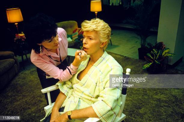 David Bowie with a makeup artist backstage 1983