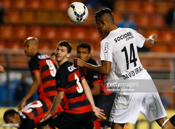 David Braz of Santos scores their first goal during the match between Santos and Vitoria for the Brazilian Series A 2014 at Pacaembu stadium on...