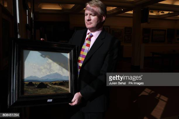 David Brittan from Adams Auctioneers with painting The Bog Road by renowned Ulster artist Paul Henry unearthed on the Antiques Roadshow and which is...