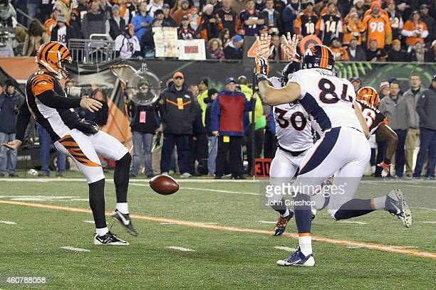 David Bruton Jr. #30 of the Denver Broncos and Jacob Tamme of the Denver Broncos attempt to block the punt of Kevin Huber of the Cincinnati Bengals...