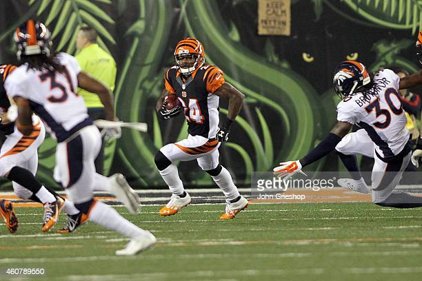 David Bruton Jr #30 of the Denver Broncos gets knocked down as Adam Jones of the Cincinnati Bengals returns a kick during the first quarter at Paul...