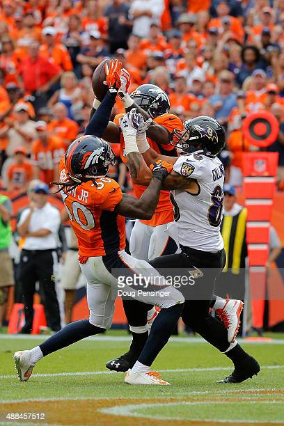 David Bruton of the Denver Broncos defends on a pass to Crockett Gillmore of the Baltimore Ravens as Darian Stewart of the Denver Broncos moves in to...