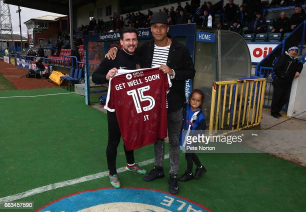 David Buchanan of Northampton Town presents a signed Northampton Town shirt to Joe Thompson of Rochdale as a show of solidarity with Thompson who has...