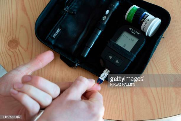 David Burns who has type 1 diabetes, uses a device to measure blood sugar levels as he prepares to adminster himself a dose of insulin in his home in...