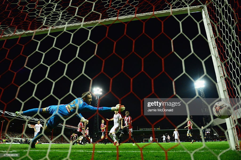 David Button of Brentford dives in vain as Fernando Amorebieta of Middlesbrough (obscured) scores their second goal during the Sky Bet Championship Playoff semi-final first leg match between Brentford and Middlesbrough at Griffin Park on May 8, 2015 in Brentford, England.