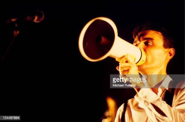 David Byrne of Talking Heads performs on stage singing through megaphone London 1982