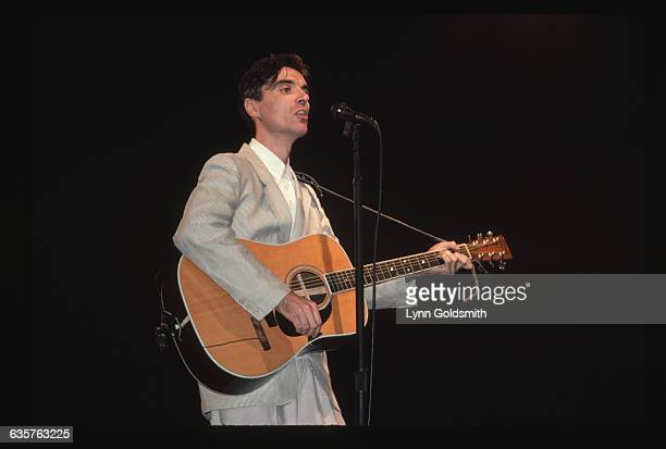 1983 David Byrne singer for the pop group The Talking Heads wears a suit and plays acoustic guitar while performing in a concert