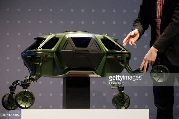 David Byron industrial design manager of SundbergFerar Inc points at the Hyundai Motor Co Elevate walking car concept as it sits on display during...