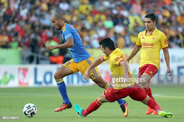David Cabrera and Diego Valdez of Morelia vie for the ball with Guido Pizarro of Tigres during their Mexican Apertura 2016 tournament football match...