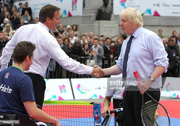 David Cameron and Boris Johnson shake hands at the end of their tennis match during the International Paralympic Day at Trafalgar Square on September...