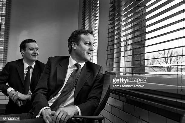 David Cameron and George Osborne pictured watching a group of media including a reporter dressed as a chicken when they visited AQL...