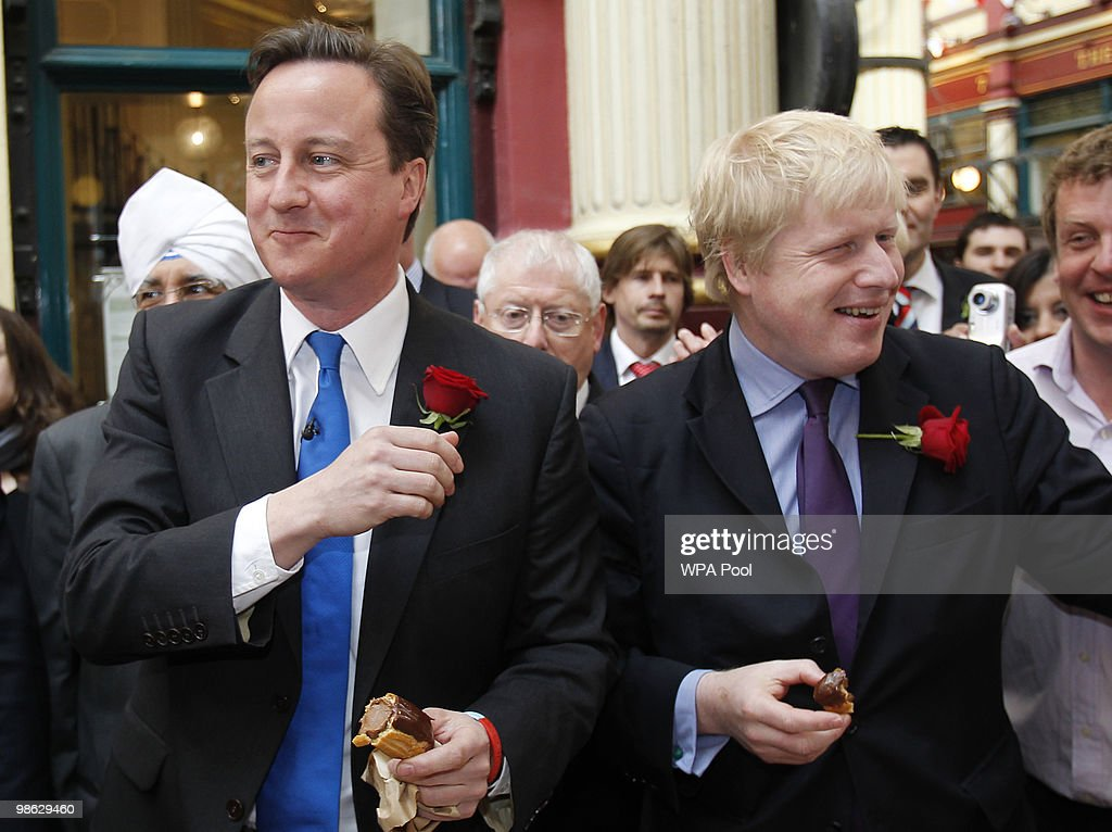 David Cameron, leader of the Conservative opposition party, and mayor of London Boris Johnson, meet members of the public and eat chocolate eclairs during St George's day celebrations, at Leadenhall Market April 23, 2010 in London. Cameron took part in the second of three live TV leader's debates last night where Prime Minister Gordon Brown claimed that the Tories would cut benefits for the elderly. The General Election, to be held on May 6, 2010, is set to be one of the most closely fought political contests in recent times with all main party leaders embarking on a four week campaign to win the votes of the United Kingdom electorate.