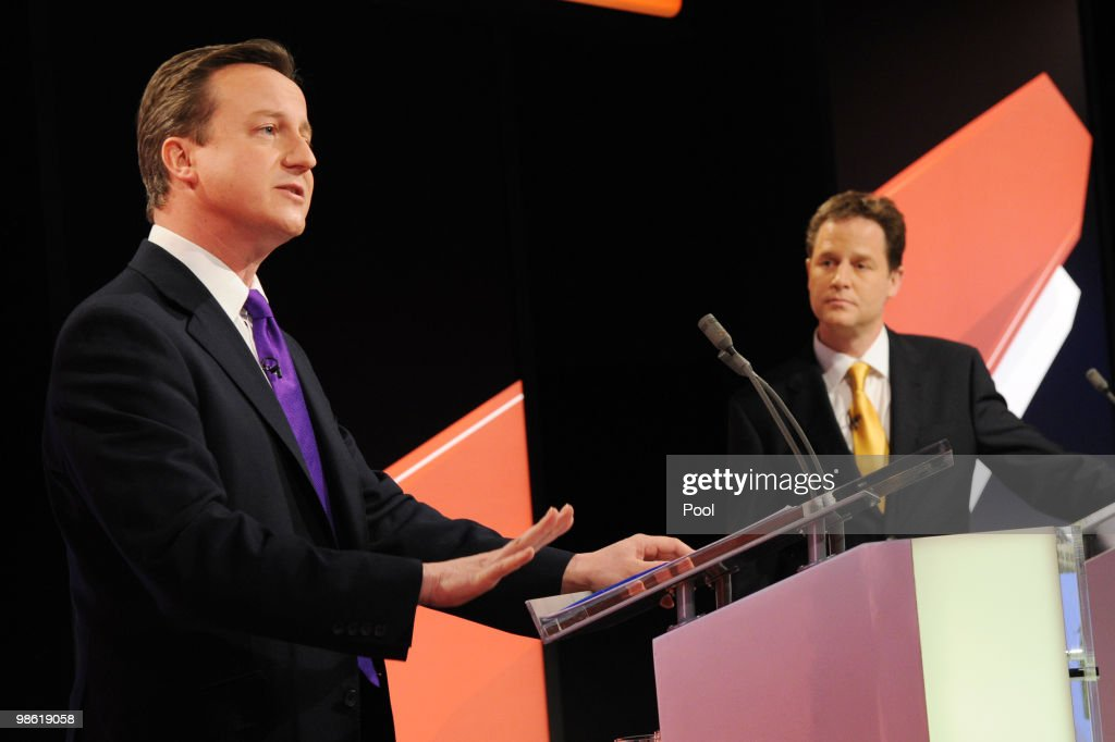 David Cameron (L) of the Conservative Party is watched by Nick Clegg (C) of the Liberal Democrats Party during the live second televised election debate on April 15, 2010 in Bristol, United Kingdom. Britain for the first time is televising three political debates live, reminiscent of the U.S. style of debates. The second of the three planned election debates, focuses on global affairs, airing live on Sky News from 20:00 BST.