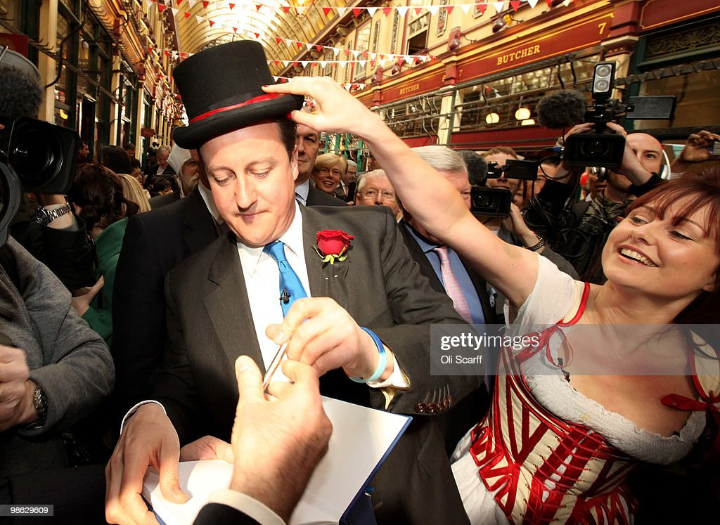 David Cameron, the leader of the Conservative party, has a top hat placed on his head by morris dancer Ellen Hobson (r) as he tours Leadenhall Market on St George's Day on April 23, 2010 in London, England. Addressing a crowd in the market Mr Cameron said he wanted to reclaim the English flag from the British National Party who are due to launch their election manifesto today.