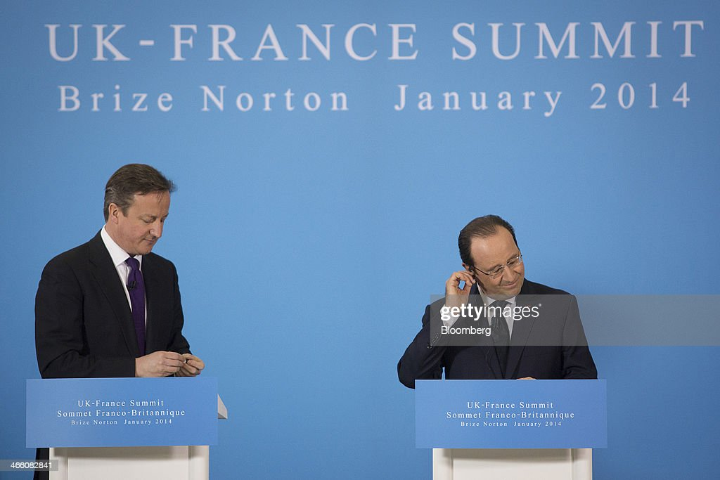 David Cameron, U.K. prime minister, left, and Francois Hollande, France's president, adjust their earpieces during a joint news conference following a UK-France summit in Brize Norton, U.K., on Friday, Jan. 31, 2014. Hollande and David Cameron met at an airbase near Oxford today to push forward industrial accords on drones, missiles and mine detectors. Photographer: Simon Dawson/Bloomberg via Getty Images