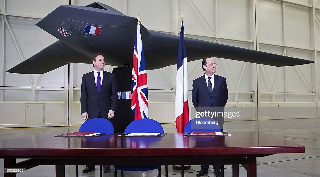 David Cameron, U.K. prime minister, left, and Francois Hollande, Frances Presidet, wait beside a model of an unmanned Future Combat Air System (FCAS) drone ahead of a signing ceremony following a UK-France summit in Brize Norton, U.K., on Friday, Jan. 31, 2014. Hollande and Cameron met at an airbase near Oxford today to push forward industrial accords on drones, missiles and mine detectors. Photographer: Simon Dawson/Bloomberg via Getty Images