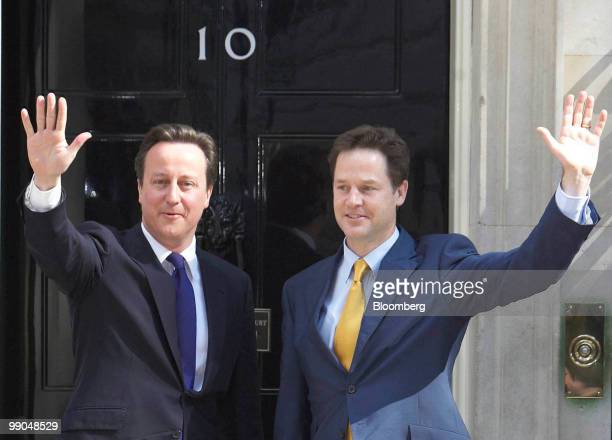David Cameron UK prime minister left and Nick Clegg UK deputy prime minister wave to the media from the steps of 10 Downing Street in London UK on...