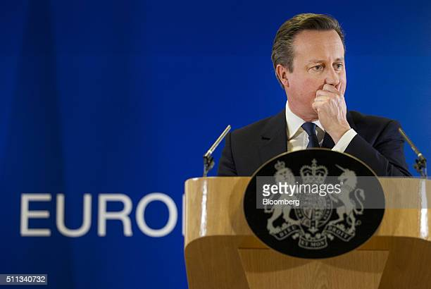 David Cameron UK prime minister listens during a news conference following a meeting of European Union leaders in Brussels Belgium on Friday Feb 19...