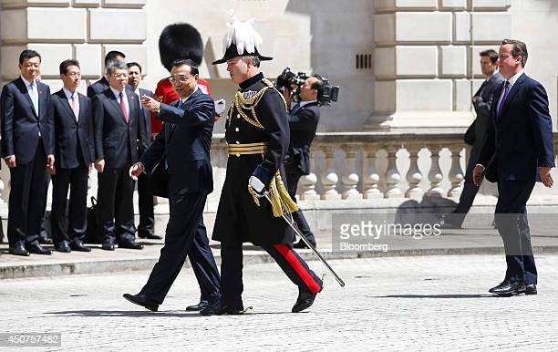 David Cameron UK prime minister right walks behind Li Keqiang China's premier center left and Edward SmythOsbourne majorgeneral of the Household...
