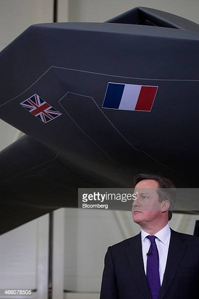 David Cameron UK prime minister stands under a model of an unmanned Future Combat Air System drone during a news conference following a UKFrance...