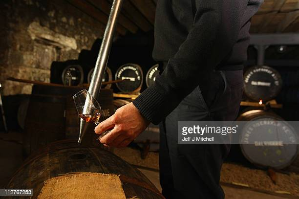David Campbell an employee at Diageo's Dalwhinnie distillery draws whisky from a cask in the store room on April 21 2011 in Dalwhinnie Scotland...
