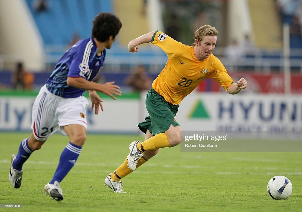 David Carney of Australia (R) gets to the ball ahead of Akira Kaji during the AFC Asian Cup 2007 Quarter Final between Japan and the Australian Socceroos at My Dinh National Stadium July 21, 2007 in Hanoi, Vietnam.