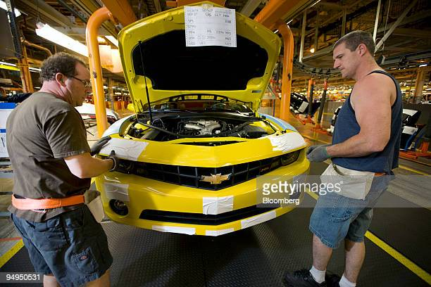 David Carty left and Jim MacLean attach the grill and bumper assemblies to a new Chevrolet Camaro on the assembly line at General Motors of Canada's...