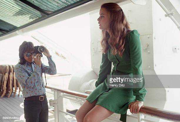 David Cassidy photographes Susan Dey as they wait on deck for their call to the set on the Fairseas cruise ship where they are filming of an episode...