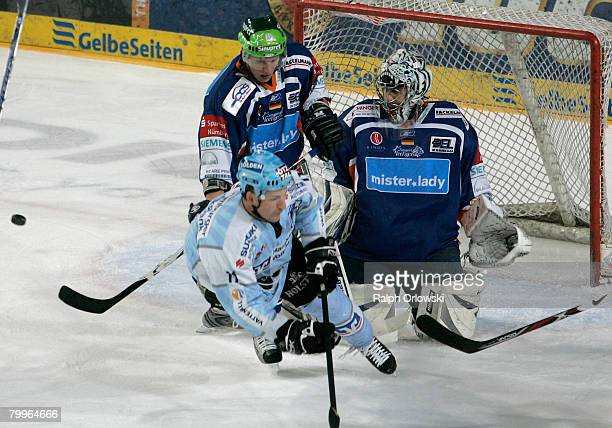 David Cespiva of Nuremberg tackles Brad Smyth of Hamburg during the DEL match between Sinupret Ice Tigers and Hamburg Freezers at the Arena...