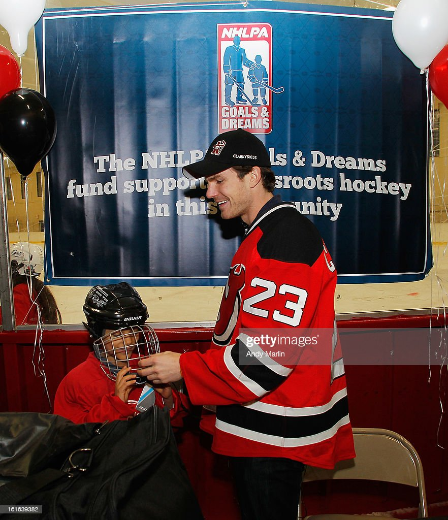 David Clarkson of the New Jersey Devils gives a helmet to a young boy during the Hockey in Newark instructional clinic during on February 13, 2013 in Newark, New Jersey.