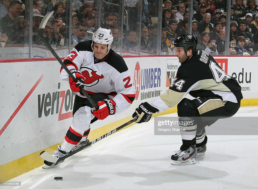 David Clarkson #23 of the New Jersey Devils moves the puck in front of Brooks Orpik #44 of the Pittsburgh Penguins on March 25, 2012 at Consol Energy Center in Pittsburgh, Pennsylvania.