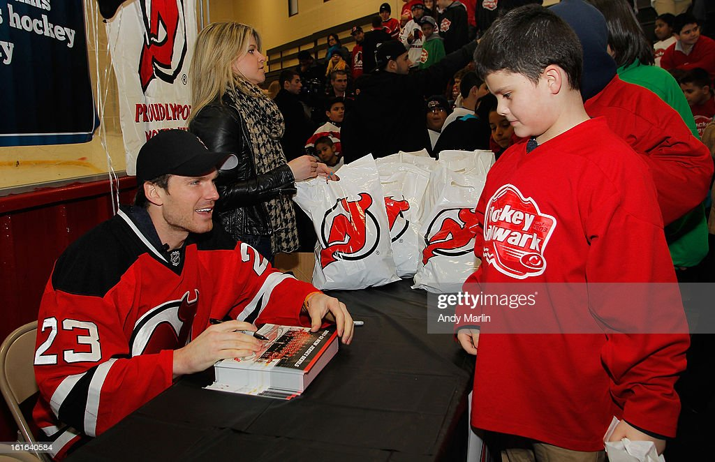 David Clarkson of the New Jersey Devils signs autographs for a fan during Hockey in Newark instructional clinic during on February 13, 2013 in Newark, New Jersey.