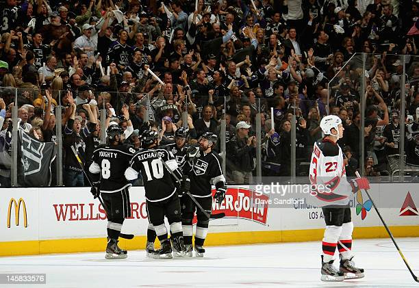David Clarkson of the New Jersey Devils skates out of the penalty box as Drew Doughty of the Los Angeles Kings celebrates with teammates after...