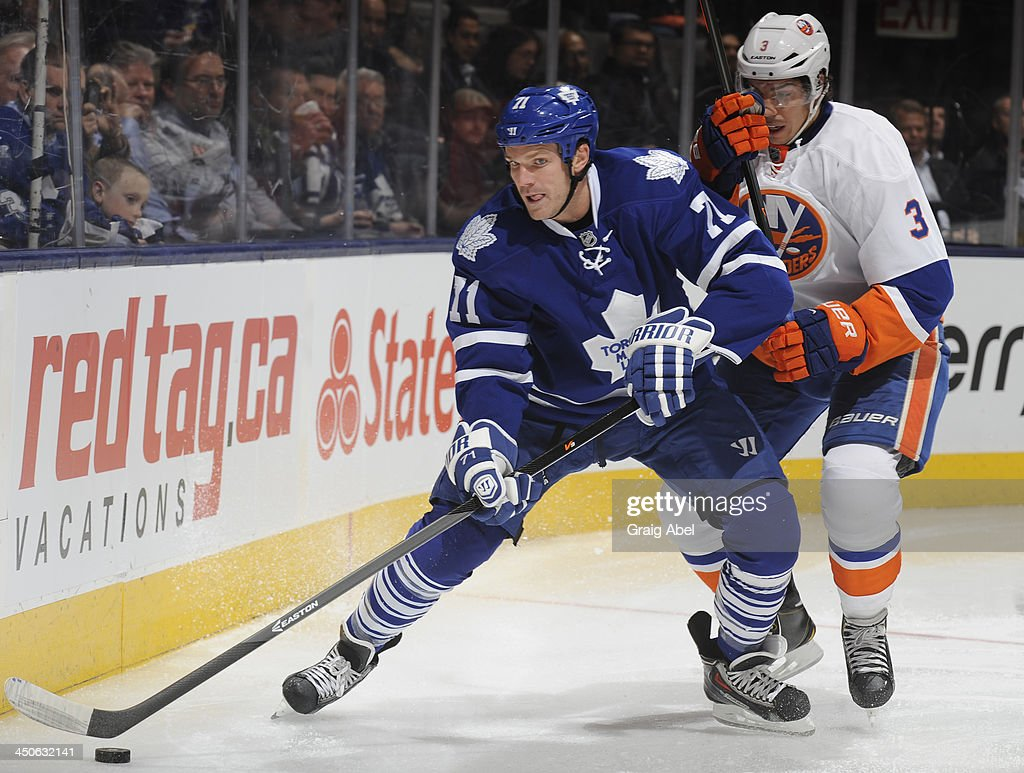 David Clarkson #71 of the Toronto Maple Leafs battles for the puck with Travis Hamonic #3 of the New York Islanders during NHL game action November 19, 2013 at the Air Canada Centre in Toronto, Ontario, Canada.
