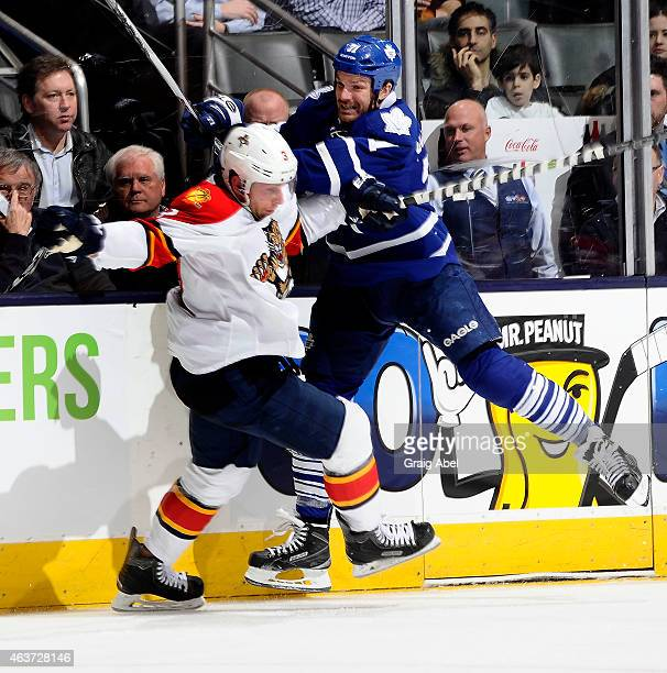 David Clarkson of the Toronto Maple Leafs runs into Steven Kampfer of the Florida Panthers during game action on February 17 2015 at Air Canada...