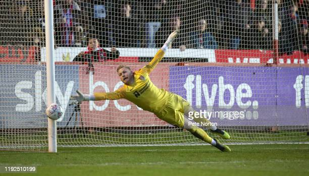 David Cornell of Northampton Town dive in an attempt to save a shot which hit the post during the Sky Bet League Two match between Exeter City and...