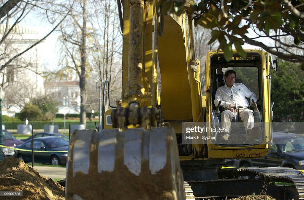 David Cos, of the Davey Tree Service waits in the cab of his bull dozer for workers to move before he can continue his heavy equipment work.